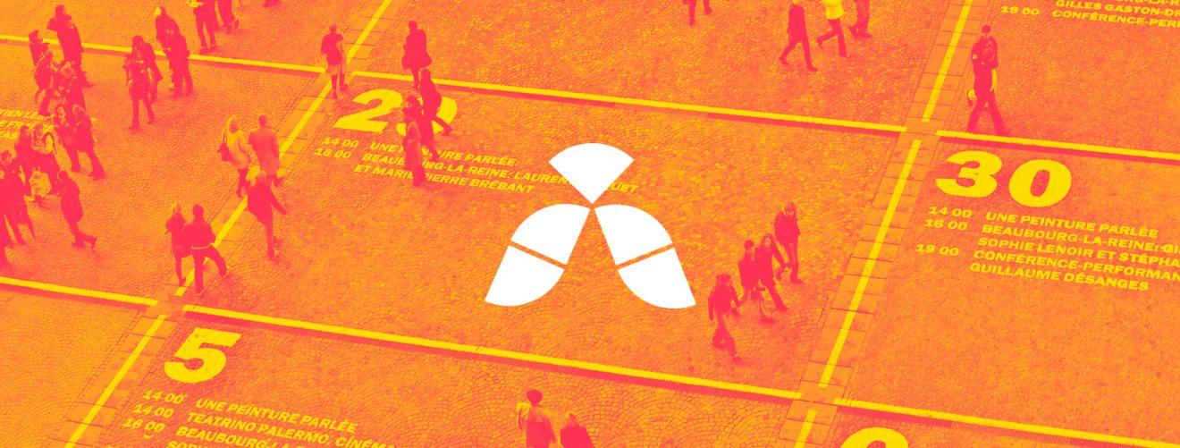 kumajan logo, taustalla ihmisiä suuren kalenterin päällä