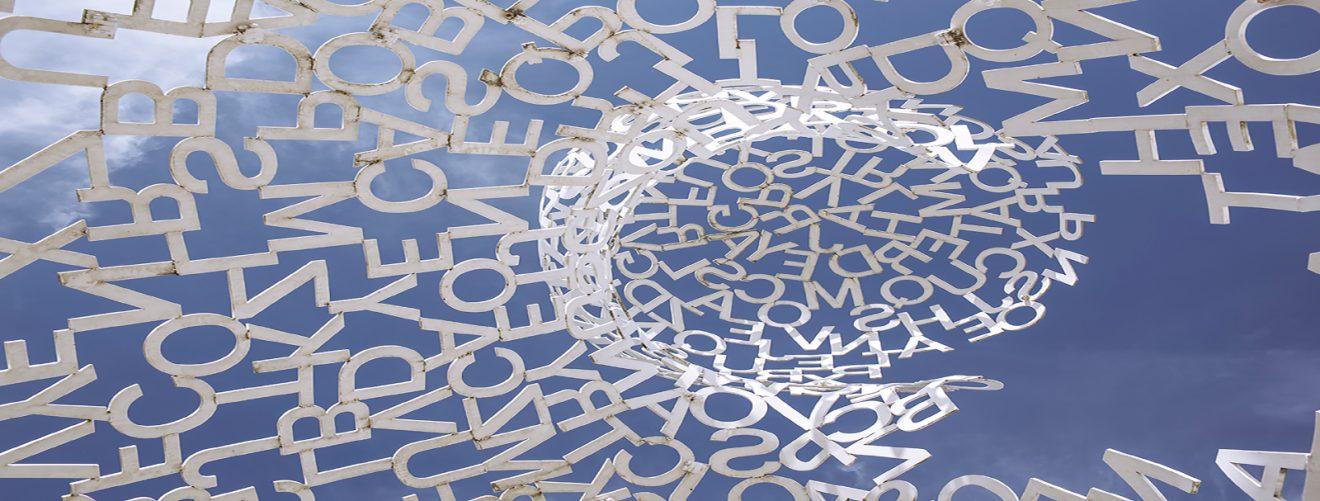 valkoisia kirjaimia veistoksena sinistä taivasta vasten