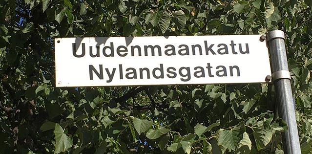 Katukyltti Uudenmaankatu-Nylandsgatan taustallaan vihreitä lehtiä