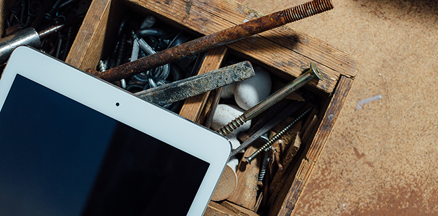 Tablettitietokone ja kuluneita työkaluja puisen työkalulaatikon päällä.